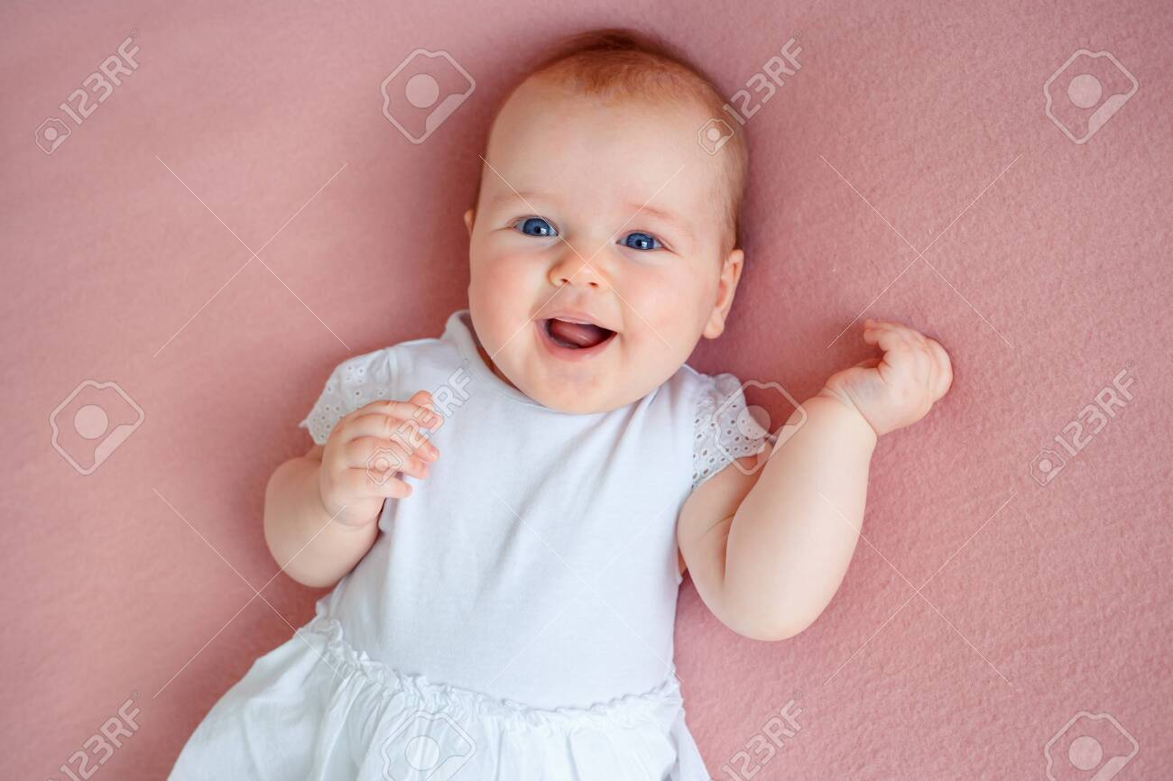 Adorable three month old baby girl in white dress lying on bed - 122164365