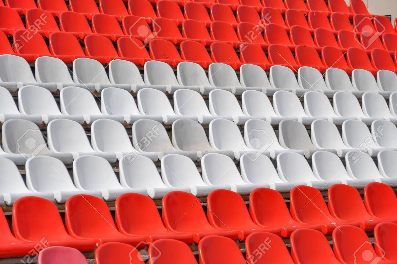 Empty seats in the stands of the arena. Rows of red and white stadium seats without spectators. The concept of the abolition of sports and mass entertainment events - 146743351