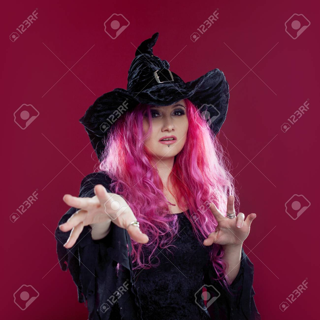 Attractive woman in witches hat and costume with red hair performs magic on a pink background  sc 1 st  123RF.com & Attractive Woman In Witches Hat And Costume With Red Hair Performs ...