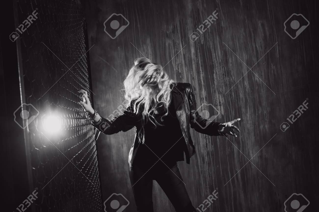 Rocknroll girl young beautiful girl dances in a dark alley