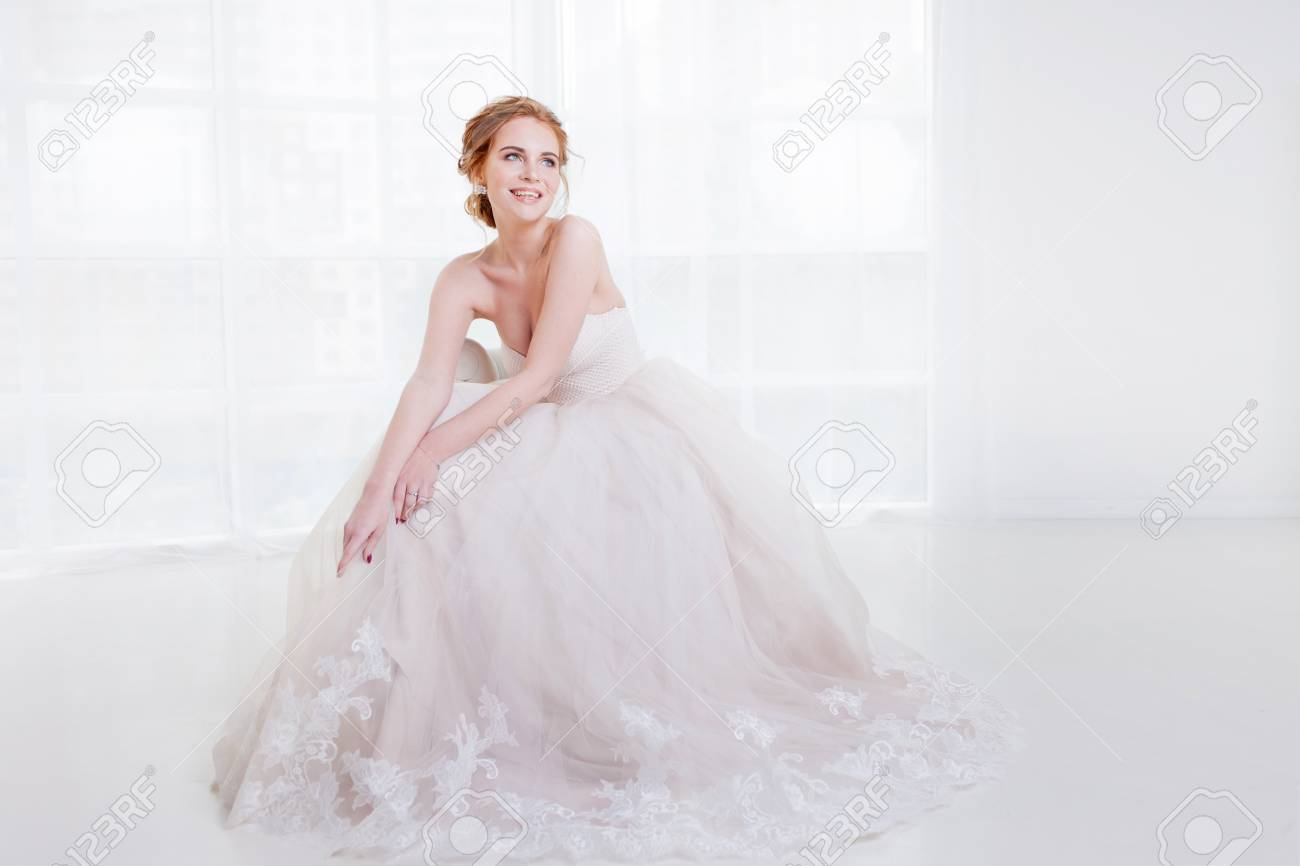 Portrait Of A Beautiful Girl In Wedding Dress Sitting On The Couch And Laughs: Haute Couture Wedding Dress Sitting At Reisefeber.org