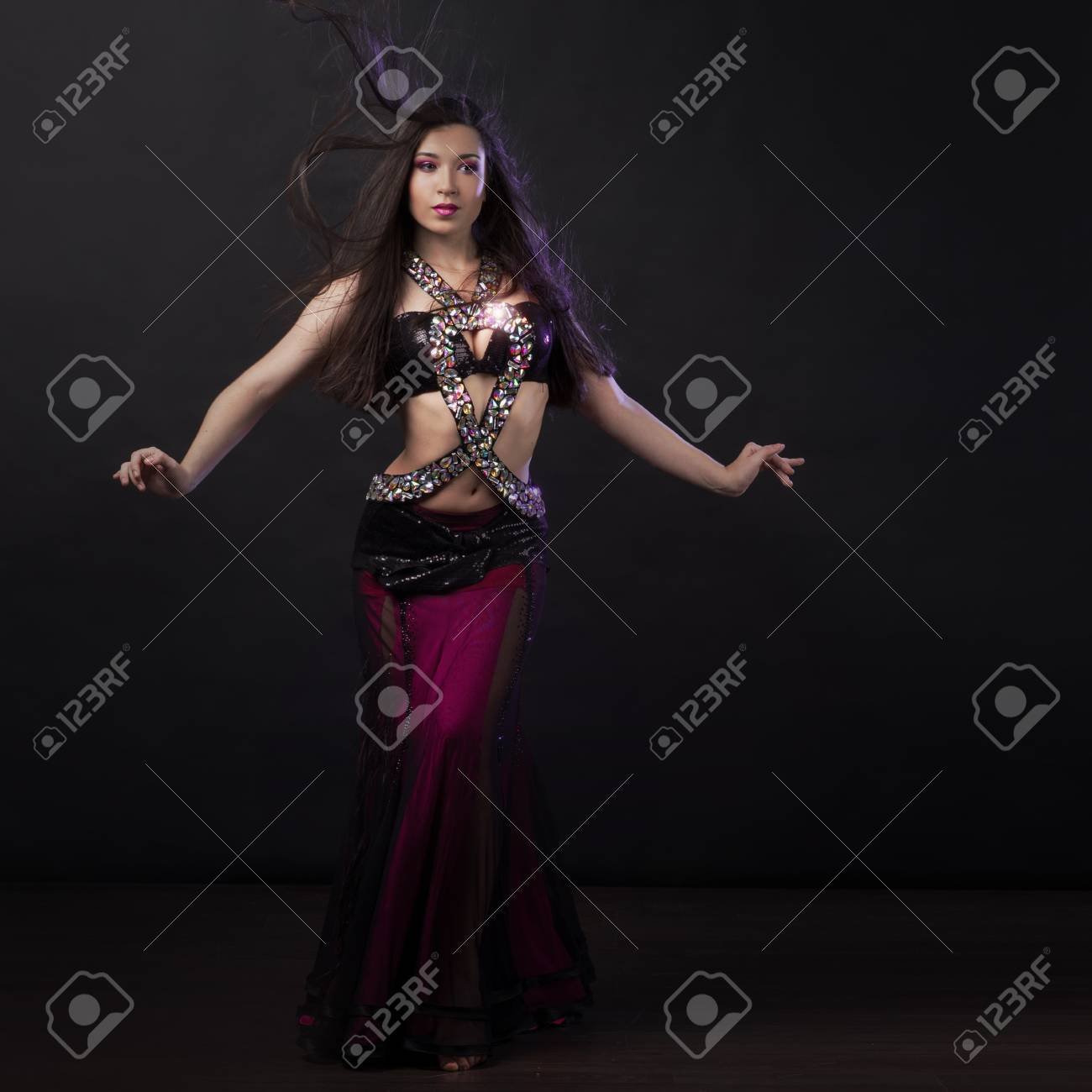 d2869fc39fa Beautiful girl in crimson dress dancing Oriental dance Stock Photo -  92557783