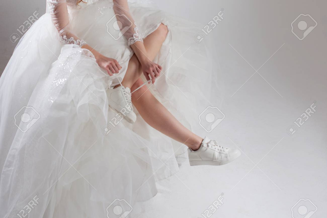 The girl in a magnificent wedding dress and white sneakers, legs..