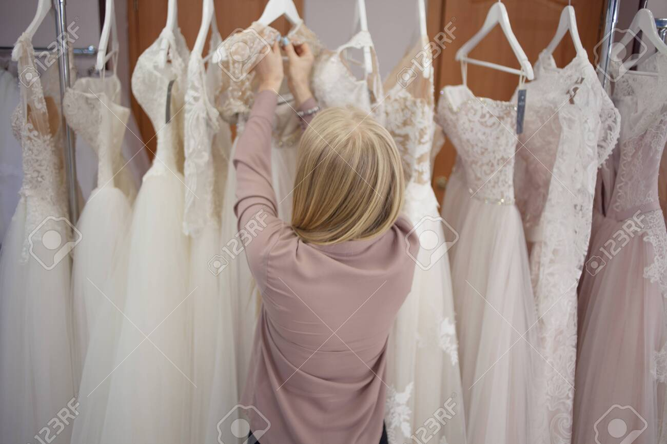 Hostess Of The Wedding Salon Looks At The Wedding Dress Small Stock Photo Picture And Royalty Free Image Image 153508730