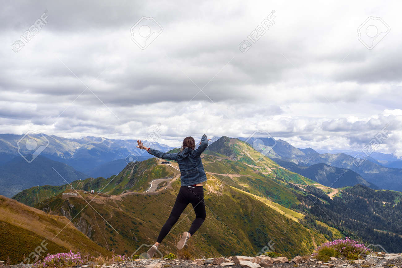 A young female tourist on top of a mountain jumps into the sky. Happiness and a sense of freedom, travel in the mountains, the power of nature - 158150747