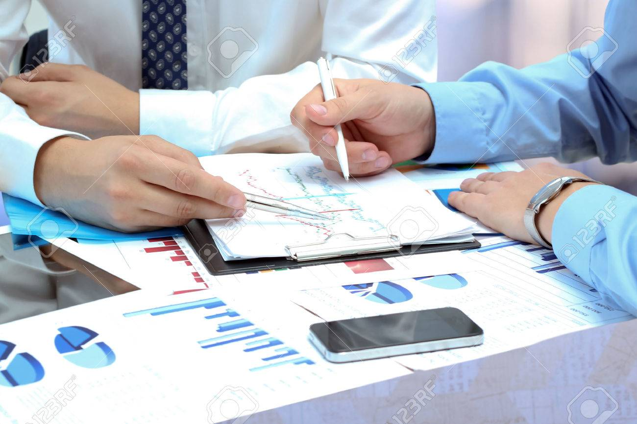 business colleagues working together and analyzing financial figures on a graphs - 36398803