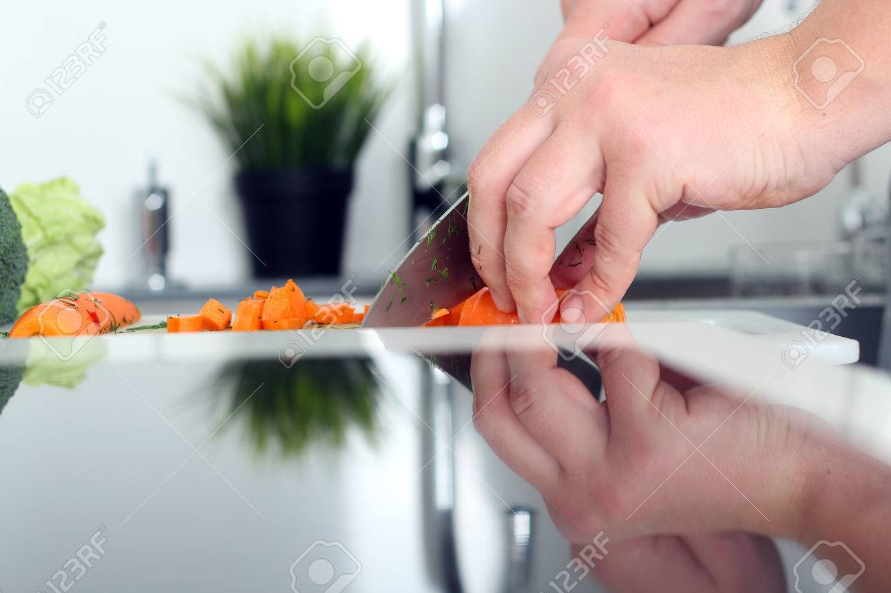 food, family, cooking and people concept - Man chopping a carrot