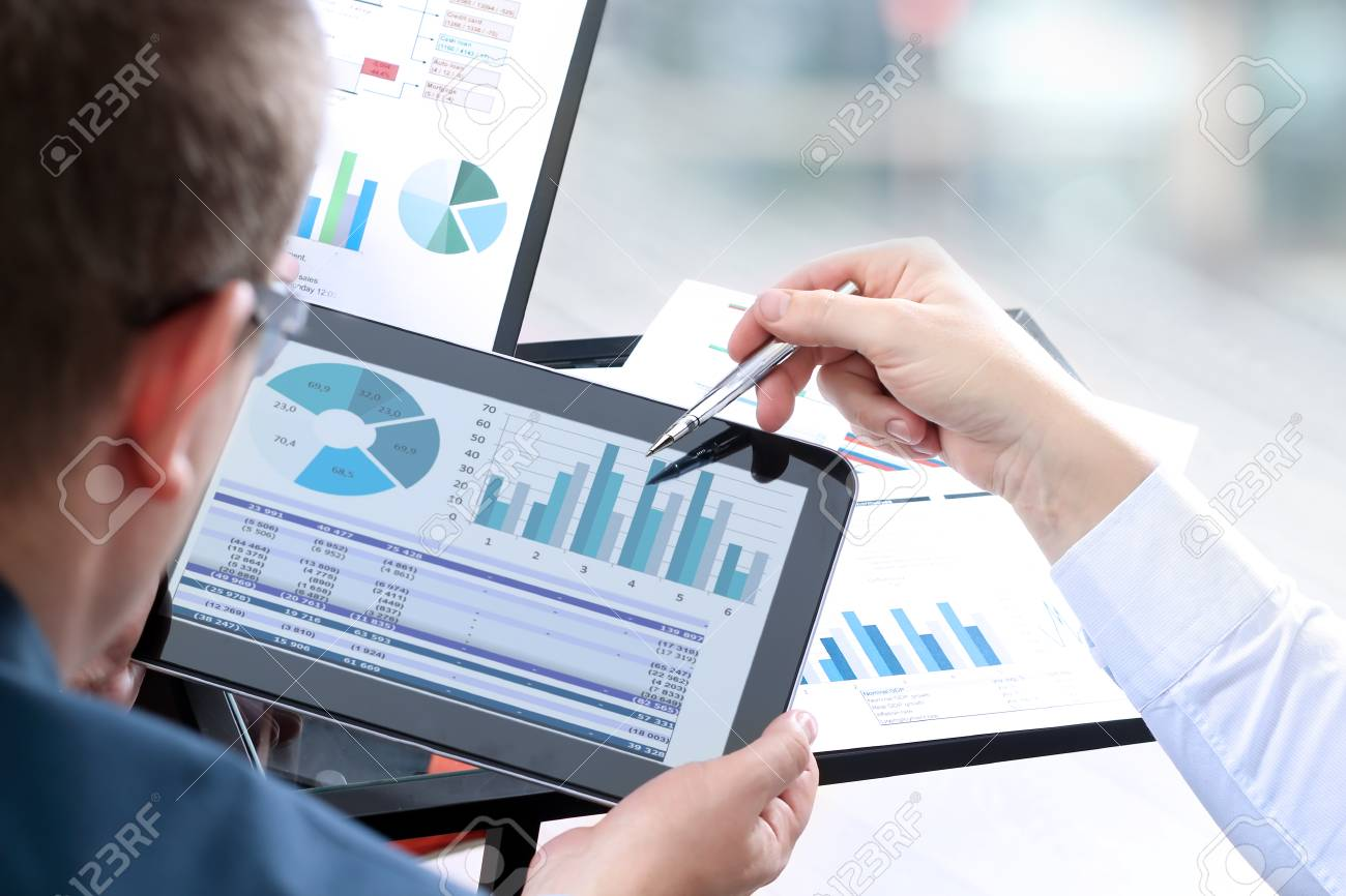 Business colleagues working and analyzing financial figures on a digital tablet - 74183670