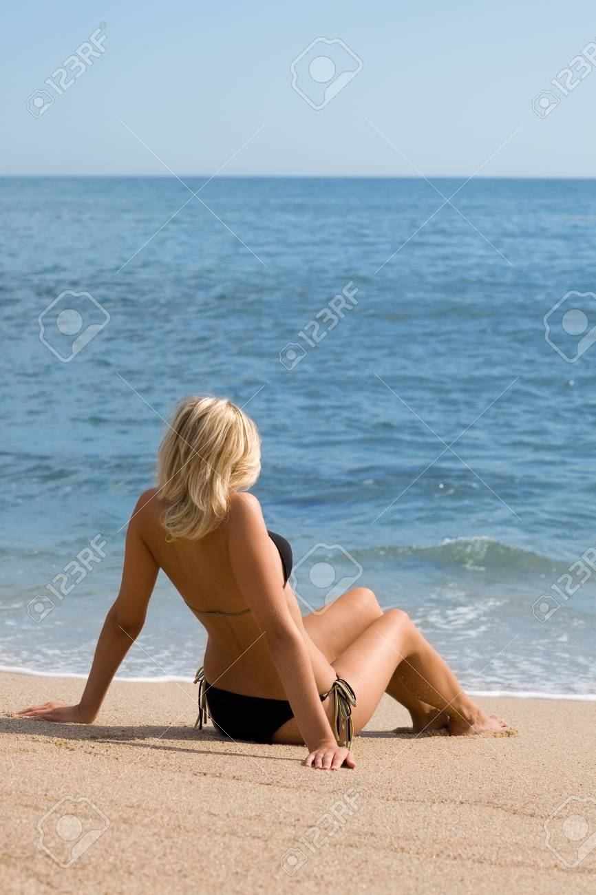 Attractive girl sitting on the sand beside the sea. Sunny day. Stock Photo - 9749292