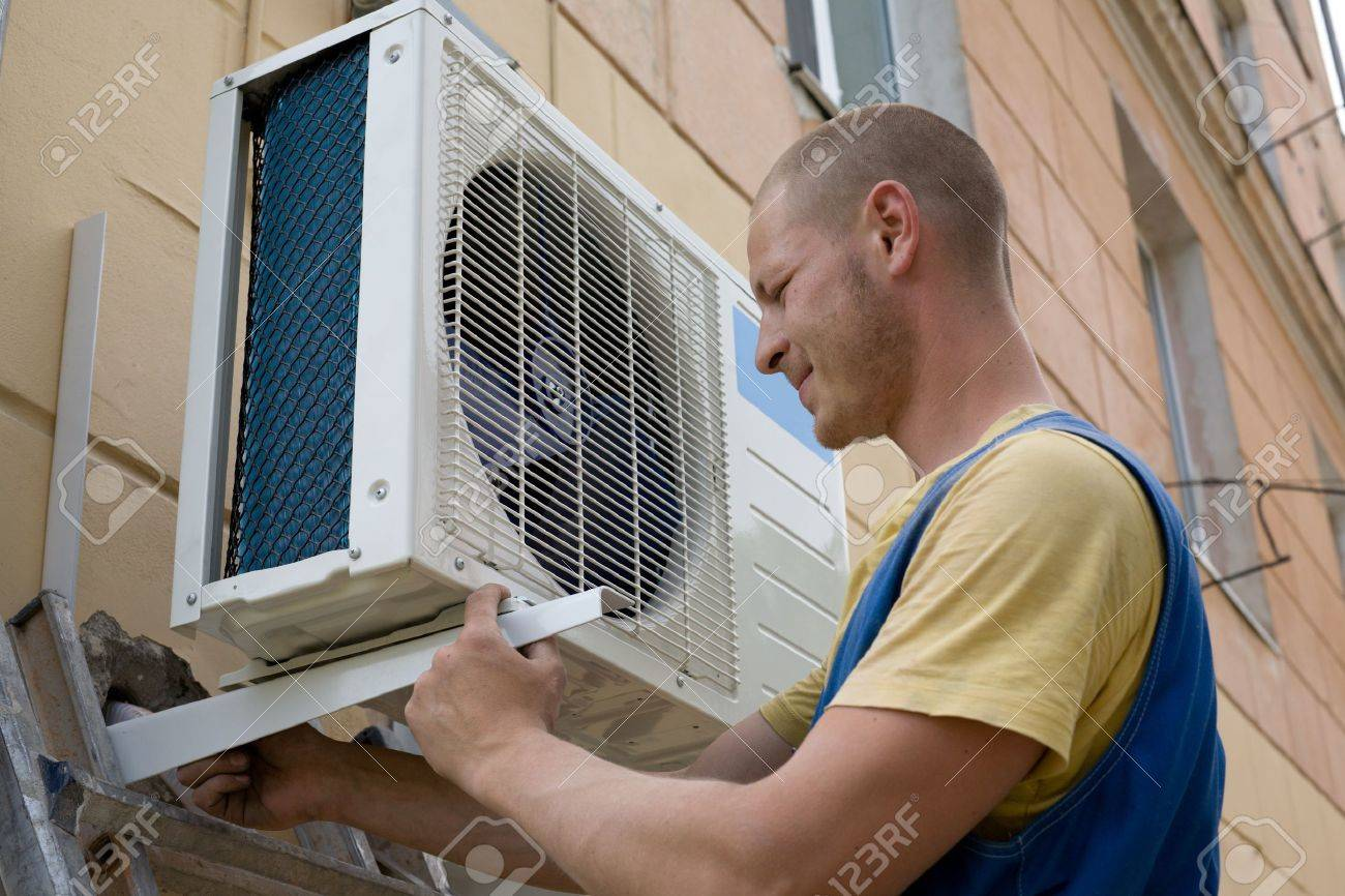 Young setup man installs the new air conditioner for office. Stock Photo - 10298847