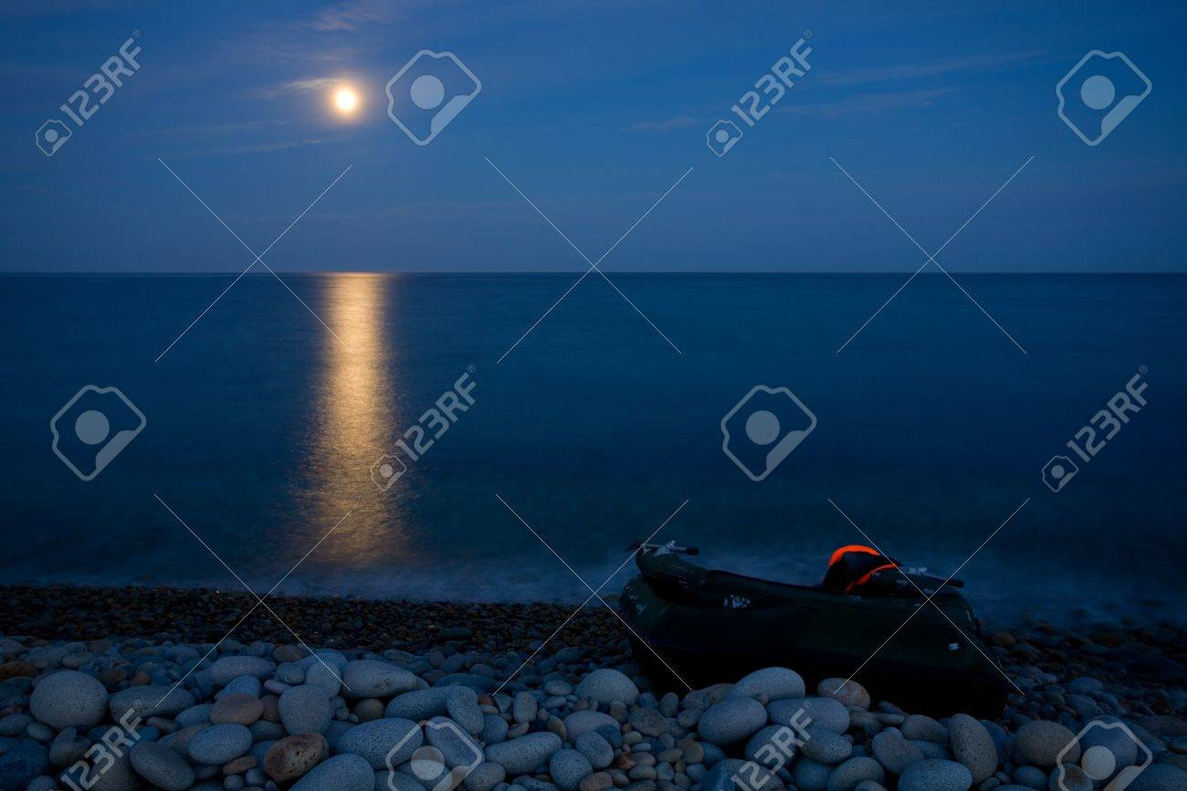 Full moon with reflection on sea. Marine rocky shore of a large pebble. On the shore of an inflatable boat. Stock Photo - 10301334