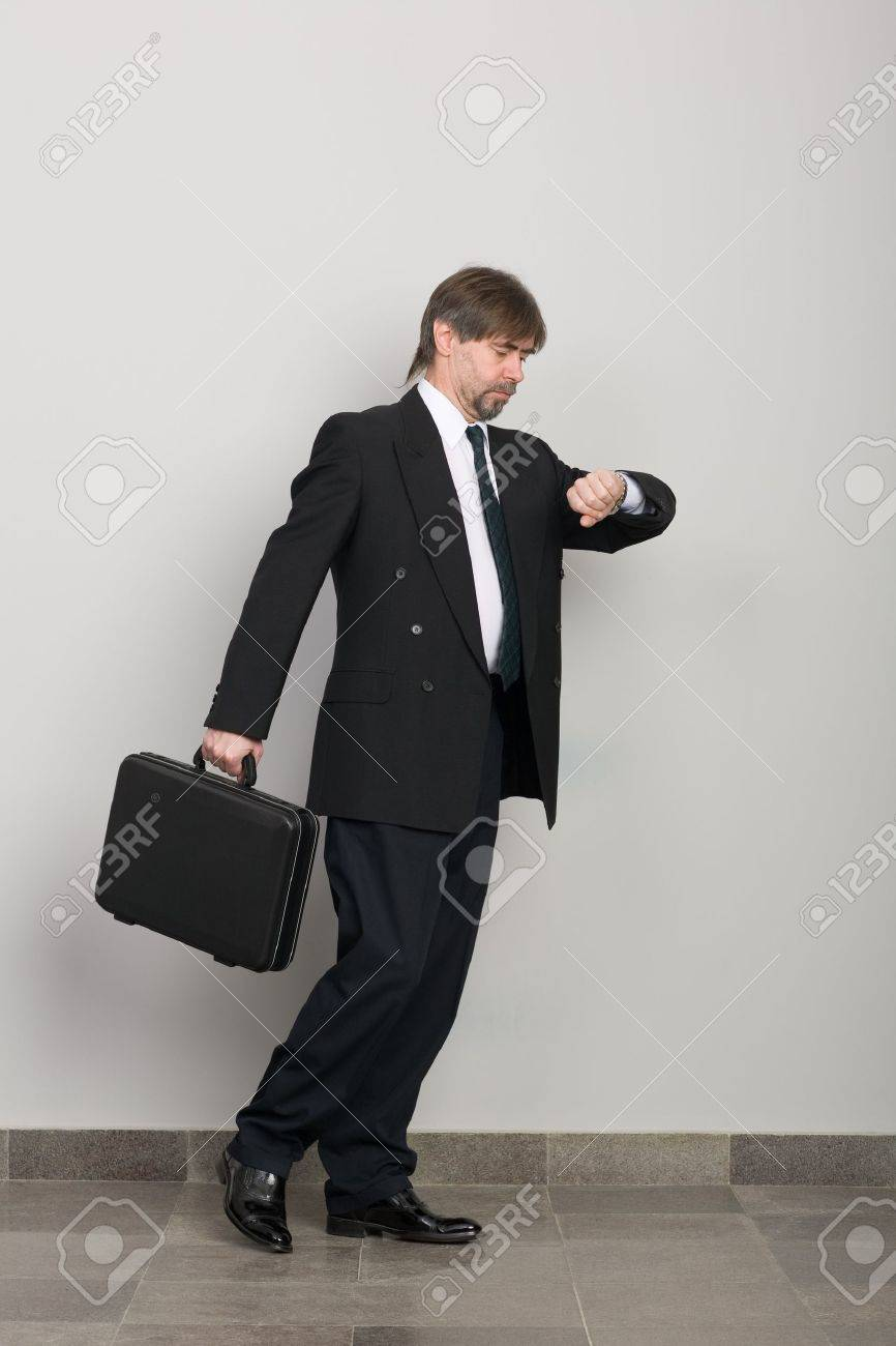 Businessman in a hurry, and looks at his wristwatch. Stock Photo - 10309386