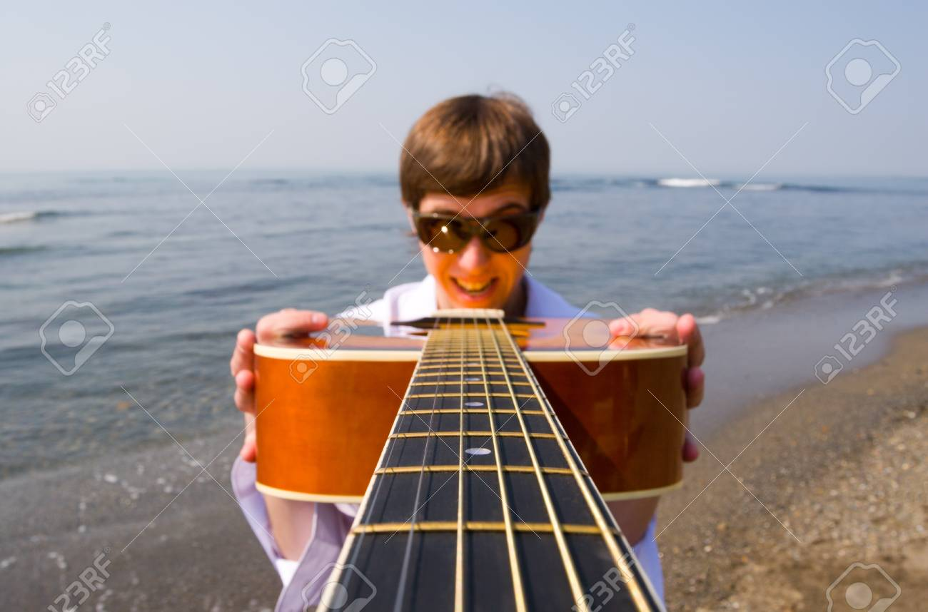 Young man (musician) holds a guitar in hands.Coast. Stock Photo - 10546210