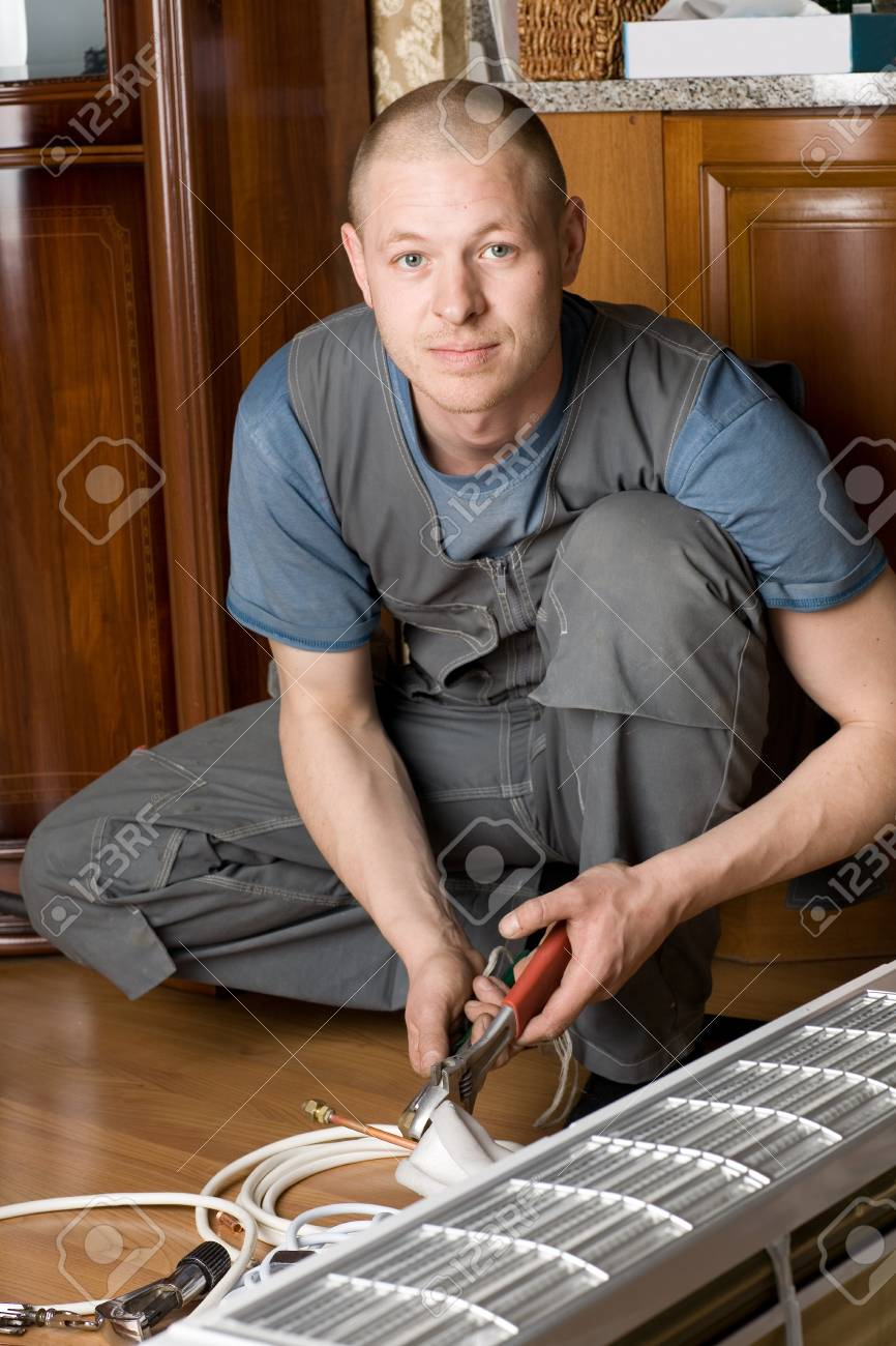 Air conditioning technician prepares a new air conditioner to be installed in the apartment. Stock Photo - 10556353