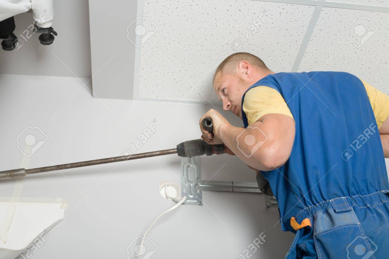 Setup man drills wall rock drill. Work on installing a new air conditioner. Stock Photo - 10574075