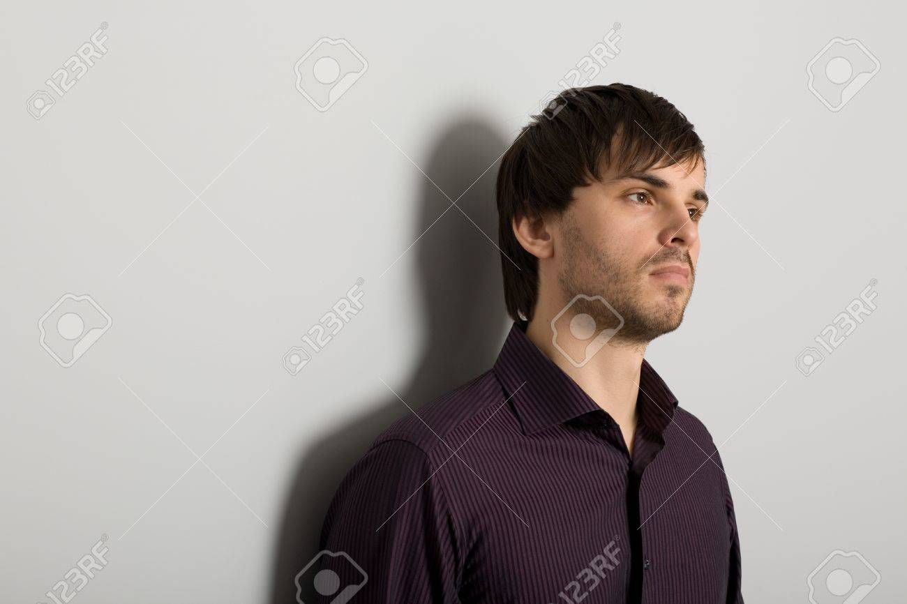 Portrait of a handsome young man looking at the background of gray wall Stock Photo - 12006249