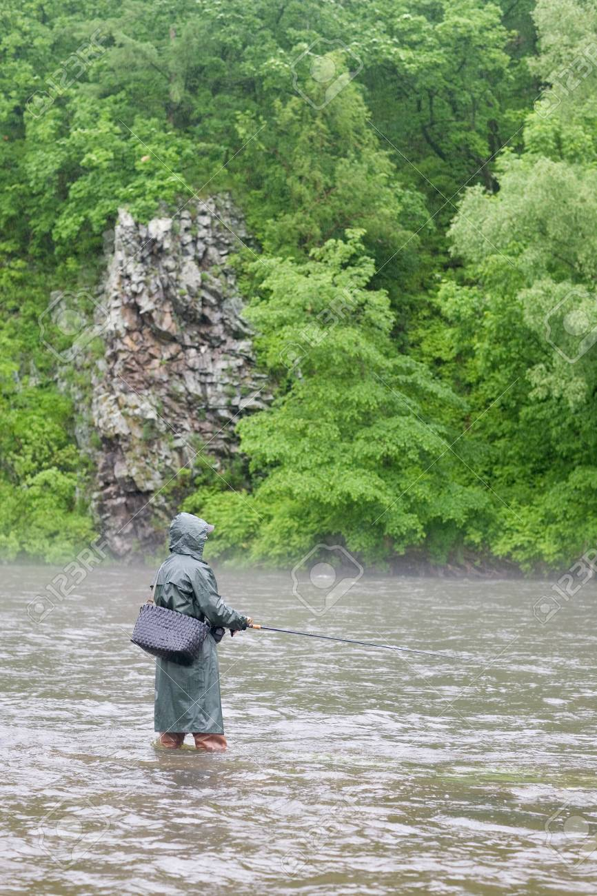 Fisherman catches of salmon on a mountain river. Is rain. Fog. Stock Photo - 12064946