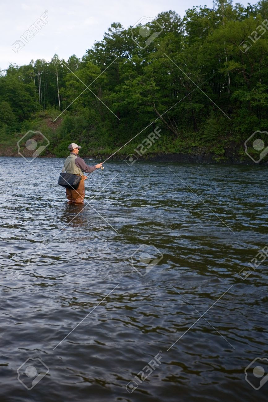 Fisherman standing in the river and catching salmon. Morning. Stock Photo - 12064942