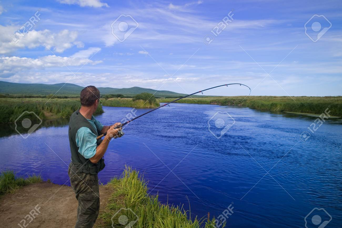 Fisherman catches of salmon (pink salmon) on the river mouth. Photographed through a polarizing filter. Stock Photo - 12600419
