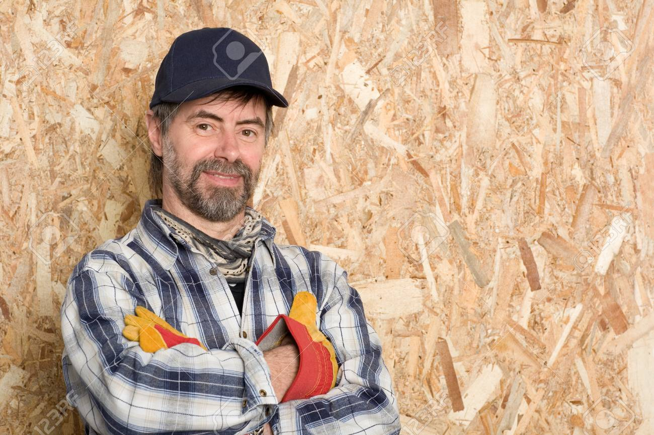 carpenter in a cap on the background sheet of plywood. Stock Photo -  13701873 55514f52ddb8
