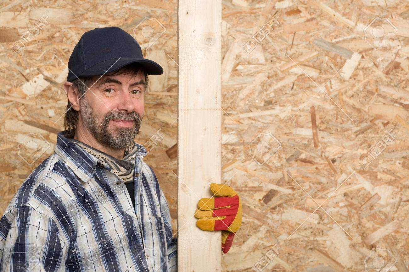 Carpenter holds a plaque on a background sheet of plywood. Stock Photo - 13701869