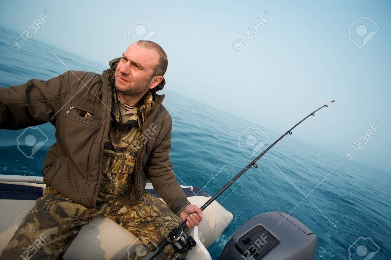 Fishing for salmon. Fisher holds a trolling rod. Stock Photo - 13718816