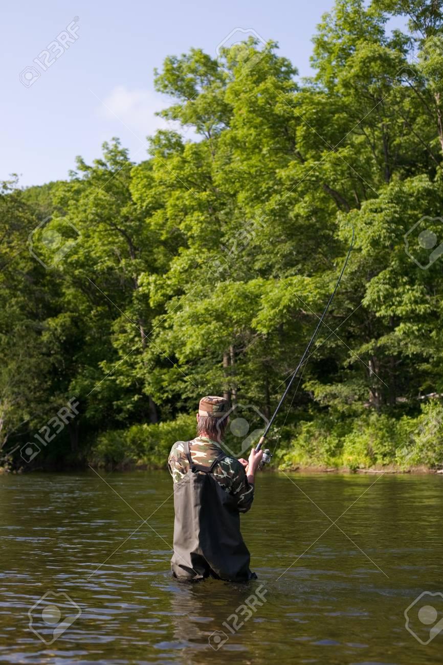 Fisherman pulls caught salmon in river. Stock Photo - 17718892