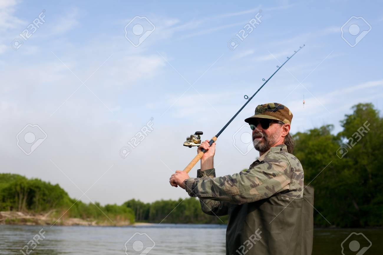 Fisherman makes casting tackle in the river Stock Photo - 17750525