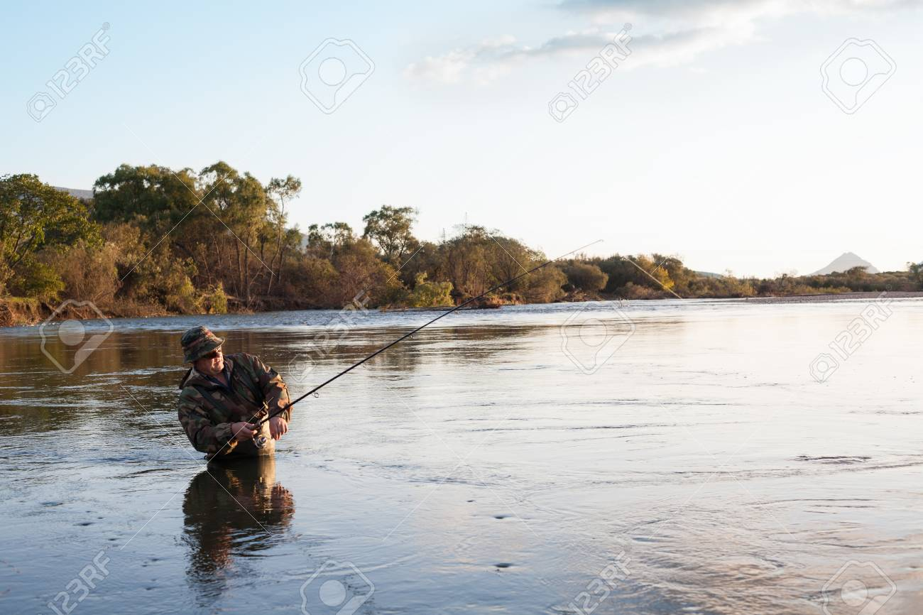 Fisherman catches of salmon in the sunset. Autumn. Stock Photo - 22813367