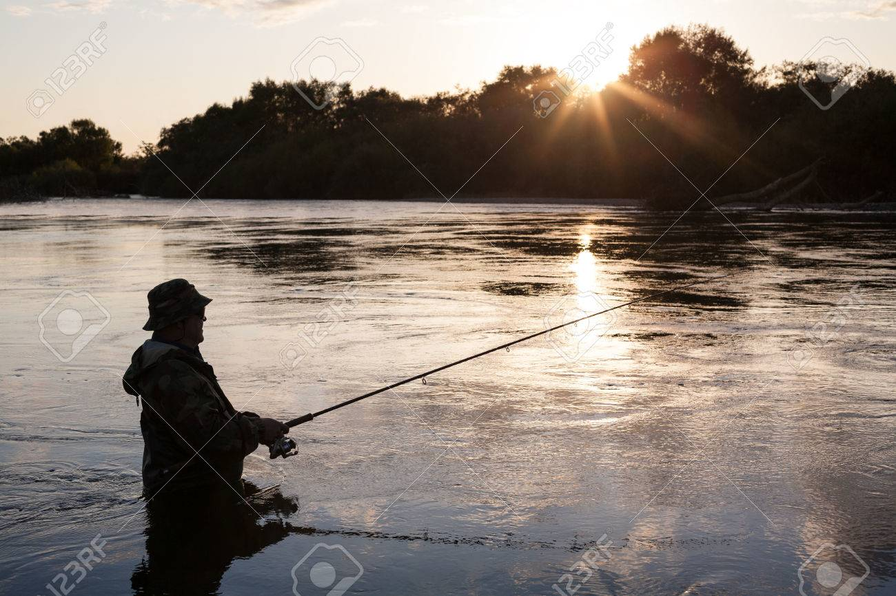 Fisherman catches of salmon at sunset in a mountain river. Autumn. Stock Photo - 22813366