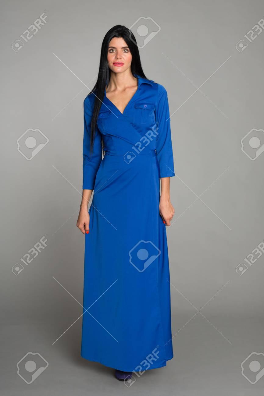 Mujer Joven Con El Pelo Negro En Un Vestido Azul Sobre Un Fondo Gris Mujer De Veinte Y Seis Años