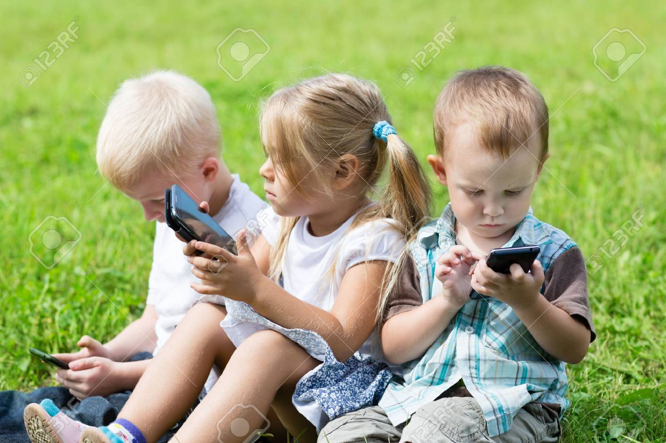 cute children using smartphones sitting on the grass in the park