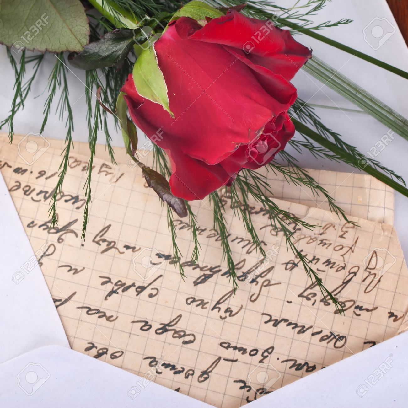 Red Rose and Letter on wooden background