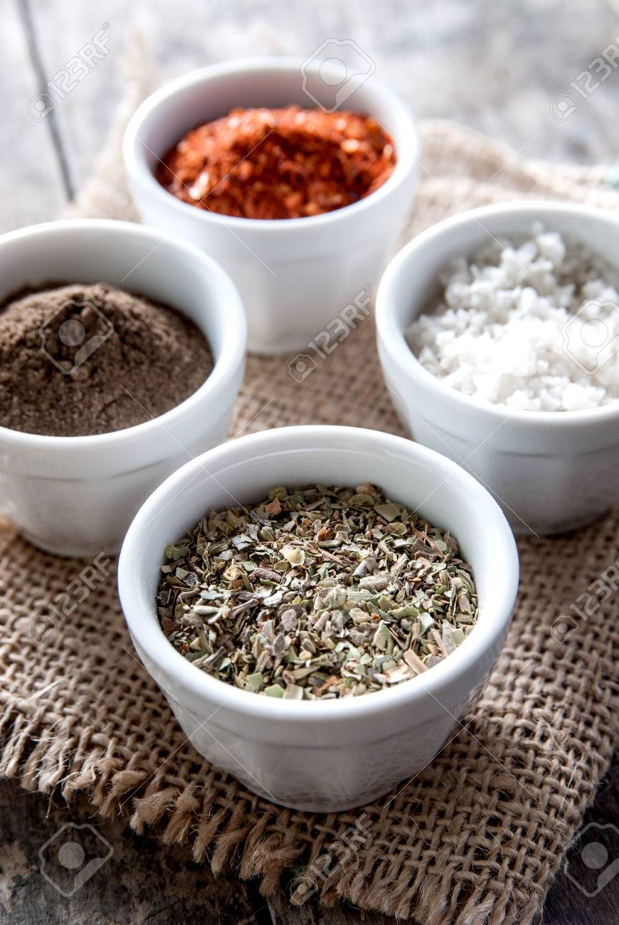 Stock Photo  Pepper, Oregano And Cooking Salt In Bowls On Rustic Wooden