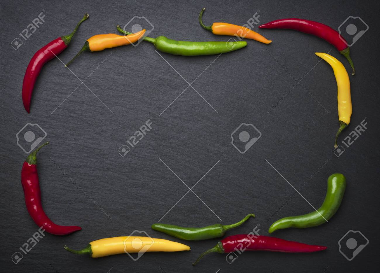 Slate framed by colorful chili peppers. - 131593499