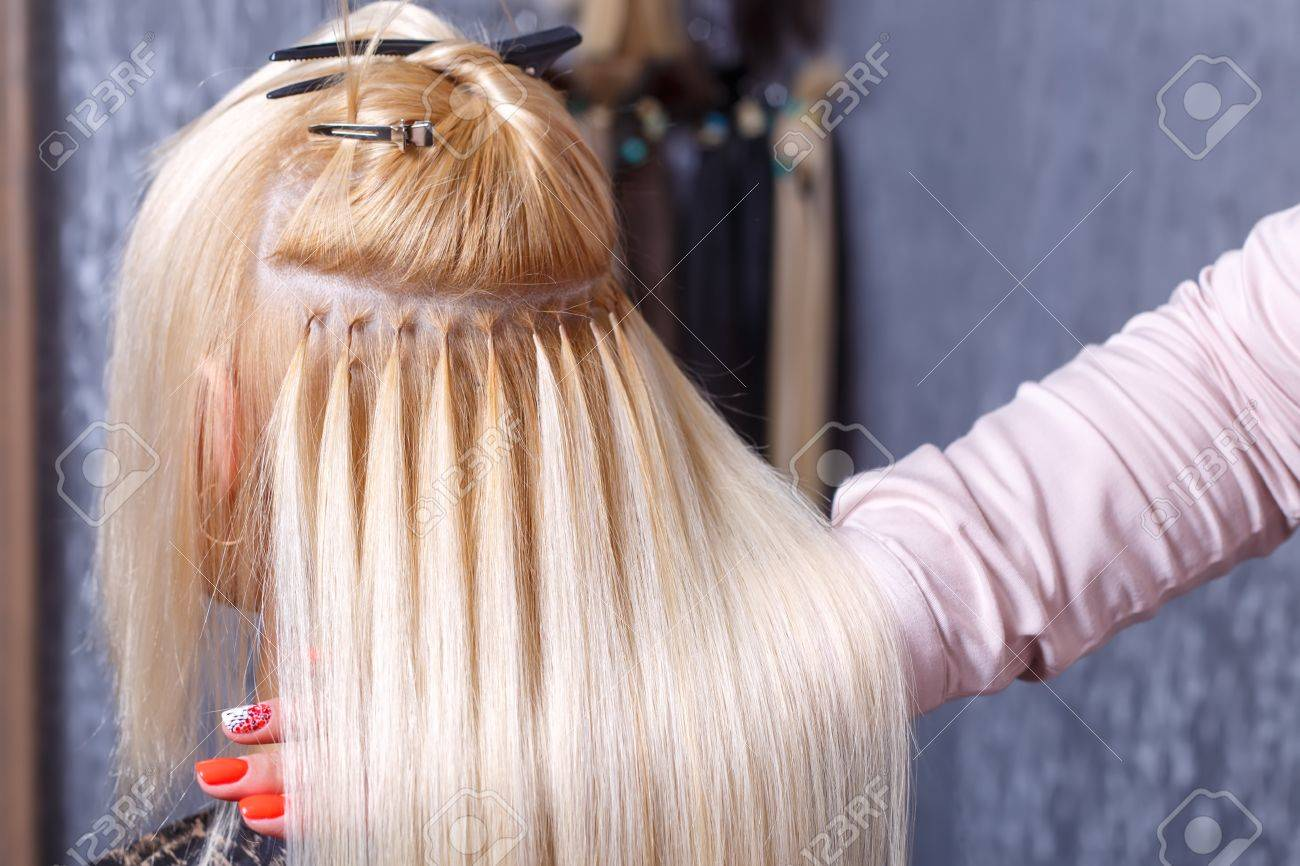 Hair extensions procedure. Hairdresser does hair extensions to young girl, blonde in a beauty salon. Selective focus. - 80230546