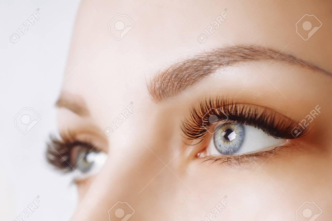 Eyelash Extension Procedure. Woman Eye with Long Eyelashes. Close up, selective focus. - 99450726