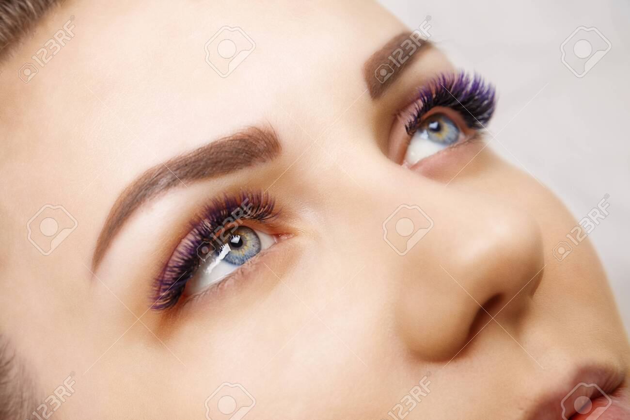 Eyelash Extension Procedure. Woman Eye with Long Blue Eyelashes. Ombre effect. Close up, selective focus. - 120994716