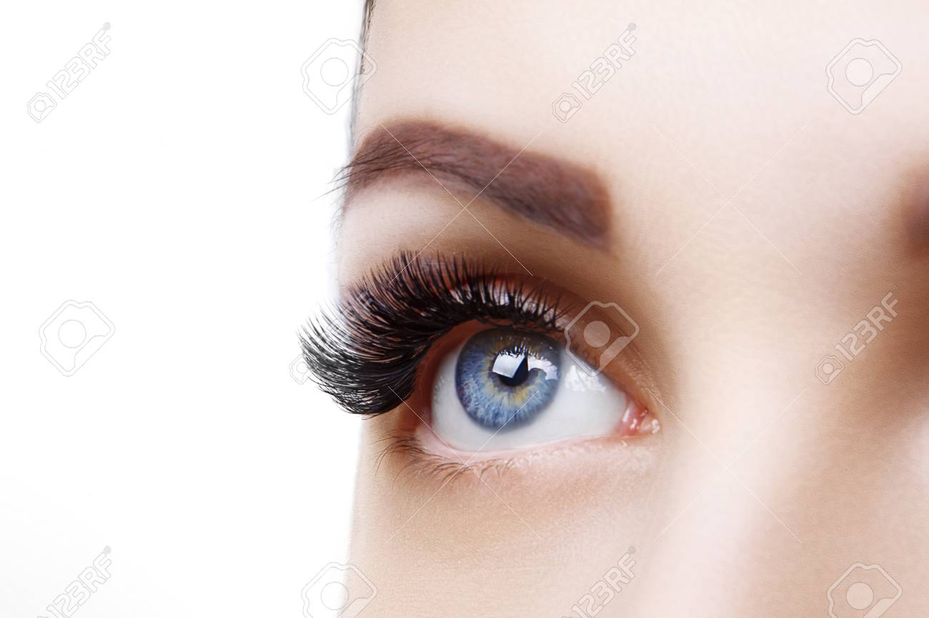 Eyelash Extension Procedure. Woman Eye with Long Blue Eyelashes. Ombre effect. Close up, selective focus. - 124798369