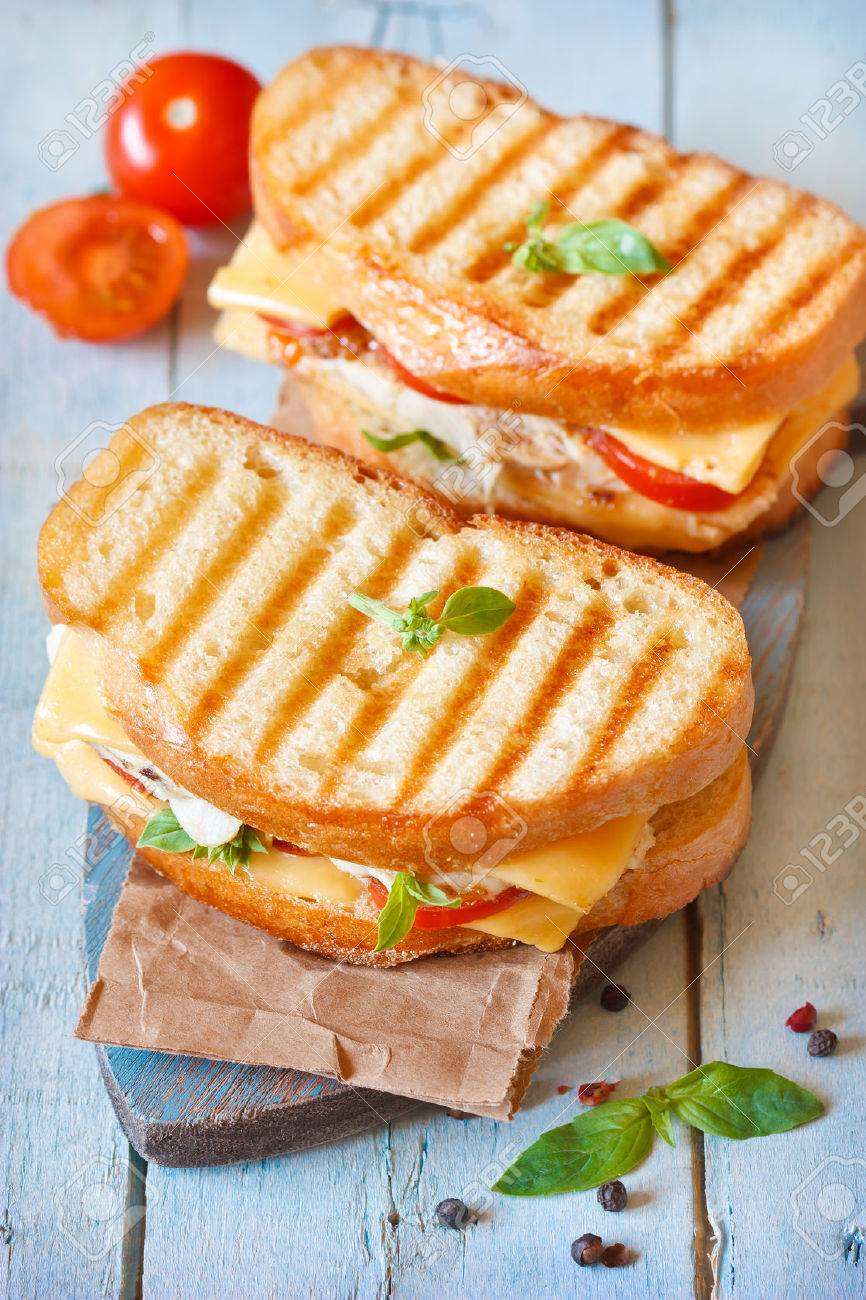 Grilled Cheese Sandwiches With Chicken And Tomatoes On A Rustic Wooden Board Stock Photo