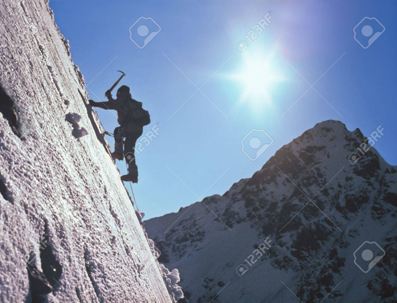 Climber  on ice slope amidst the high mountains and the bright sun Stock Photo - 20313758
