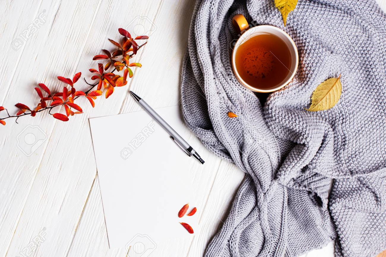 Autumn flatlay on wooden backdrop with a cup of tea and fallen dry yellow and red leaves. Free space for text. Cozy home concept - 88455357