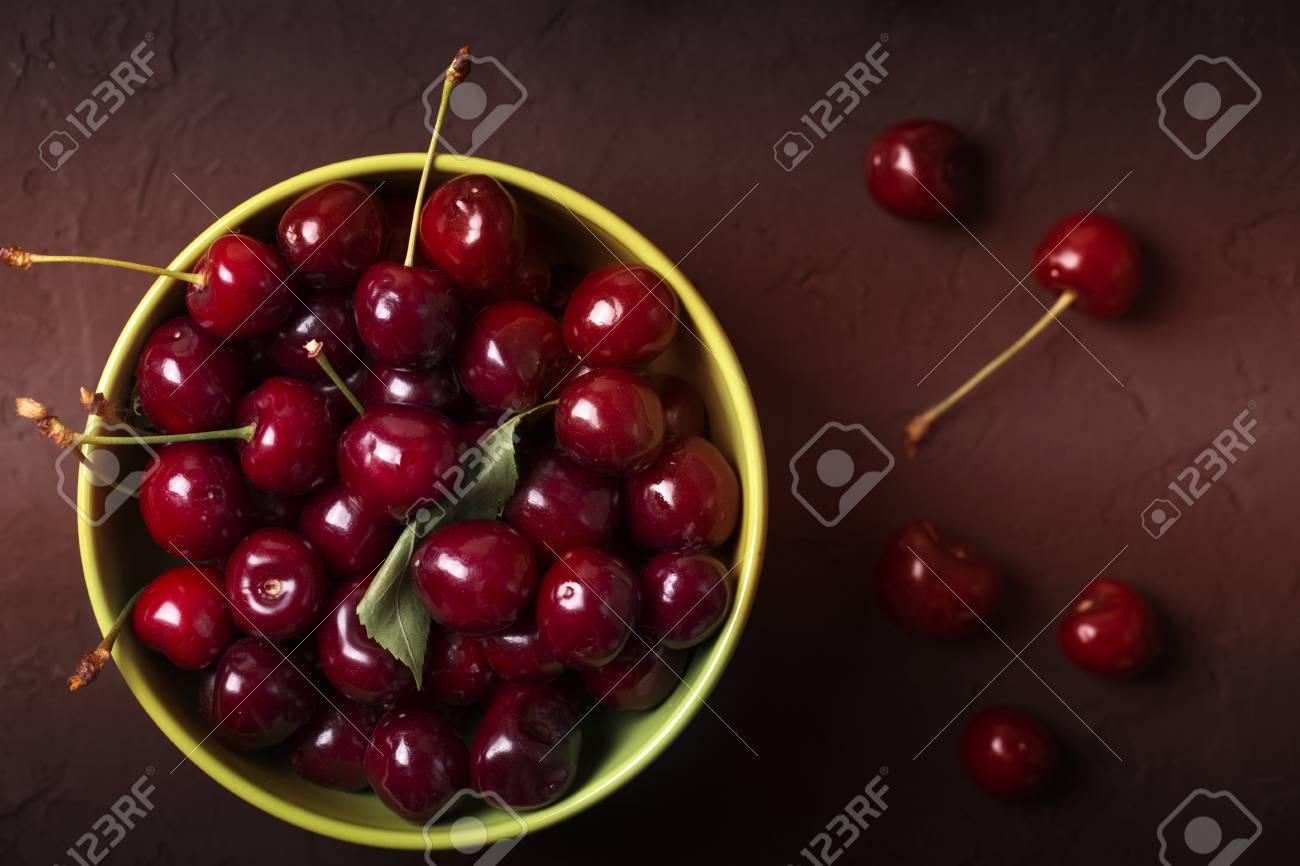 Fresh cherries in bowl on table  Fresh cherries in pot on the