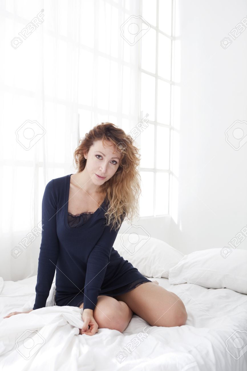 woman kneeling in bed holding the sheets stock photo picture and