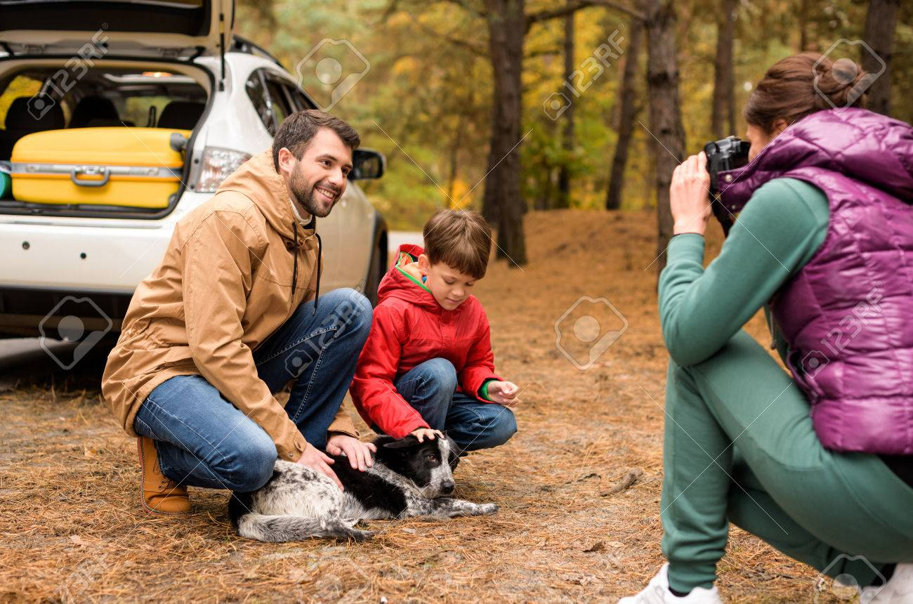 Happy Family Playing With Funny Dog Near White Car Open Trunk In Autumn Forest Stock