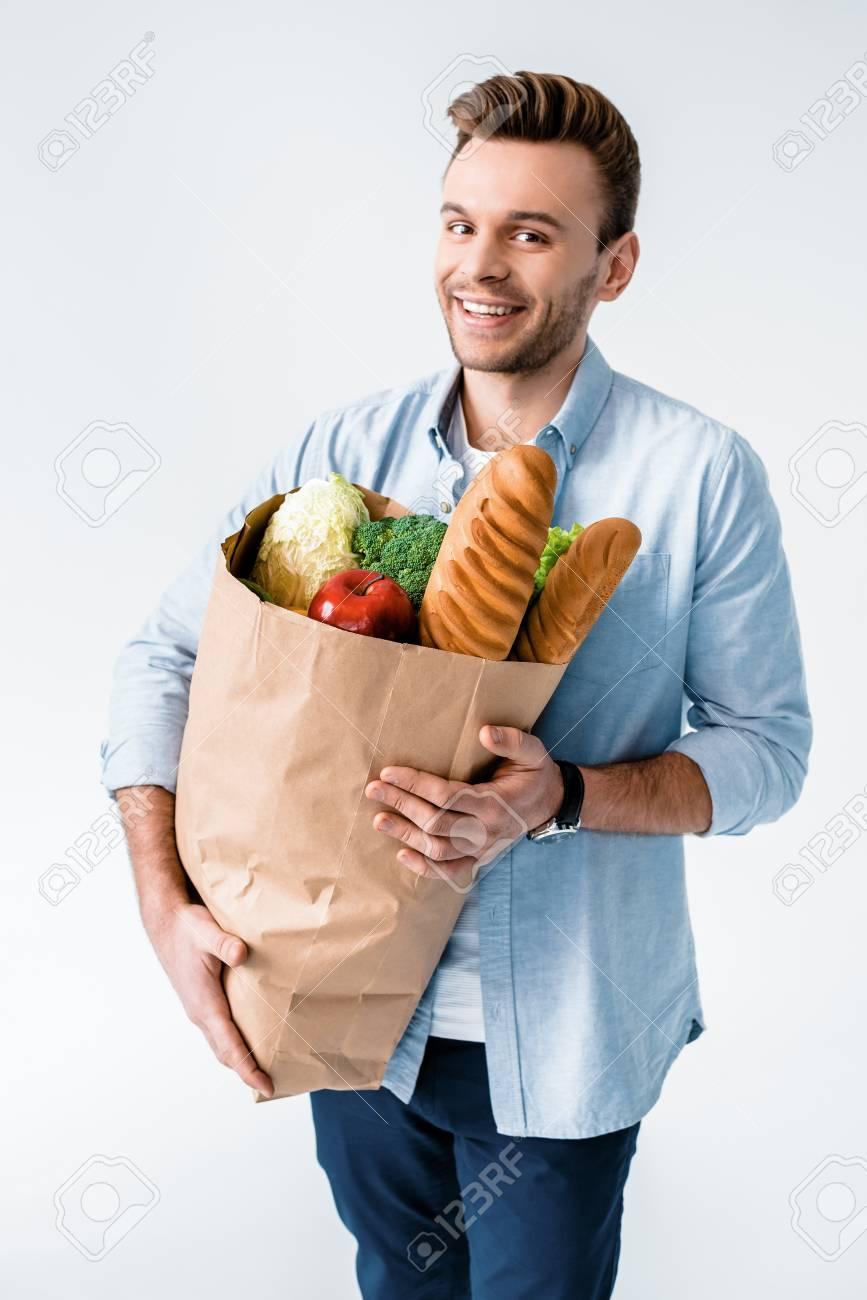 Hombre sosteniendo la bolsa de supermercado con productos y sonriendo a la cámara