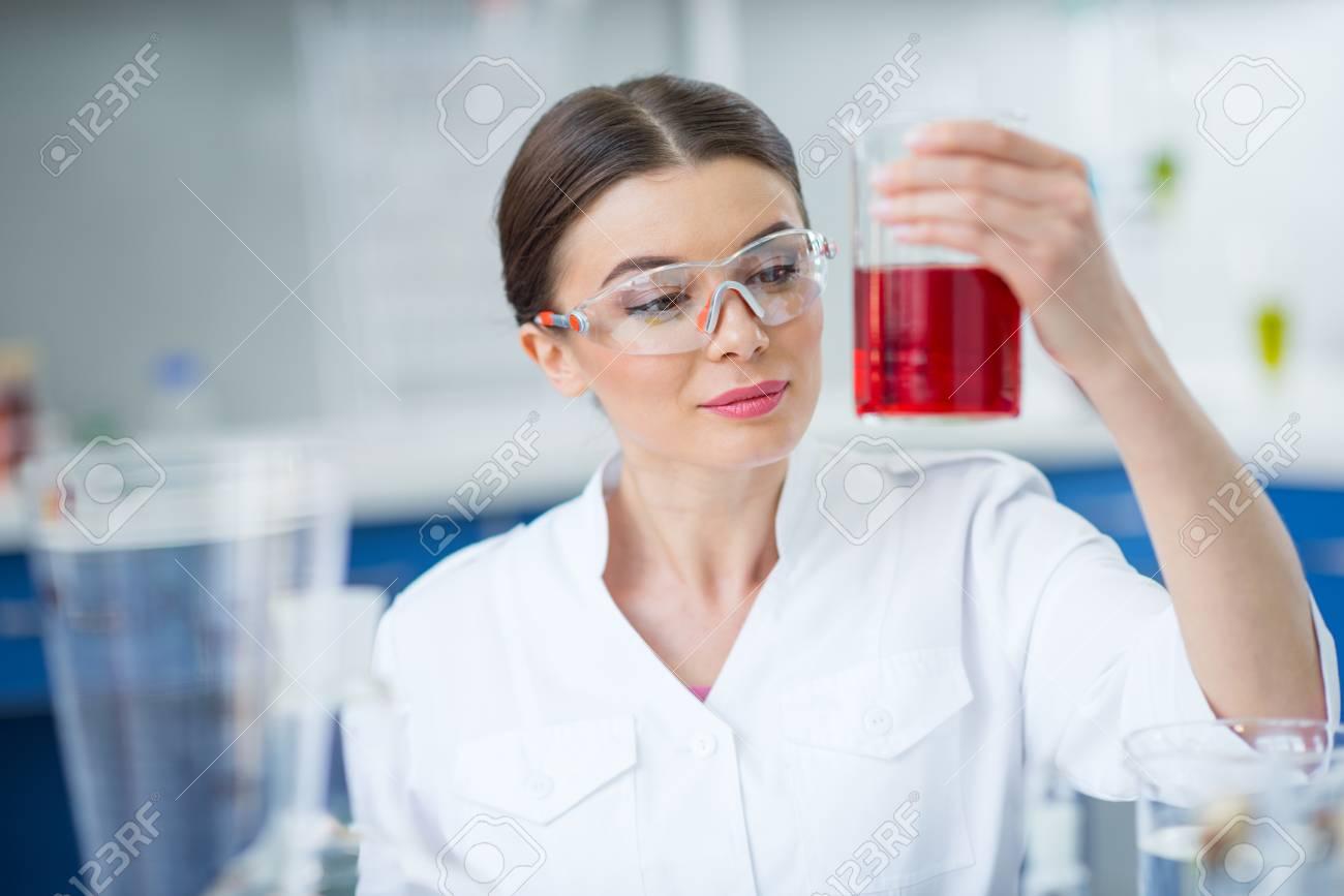 Banque d images - Souriant femme scientifique en vêtements de travail de  protection tenant la fiole avec le réactif f333ac1ebb00