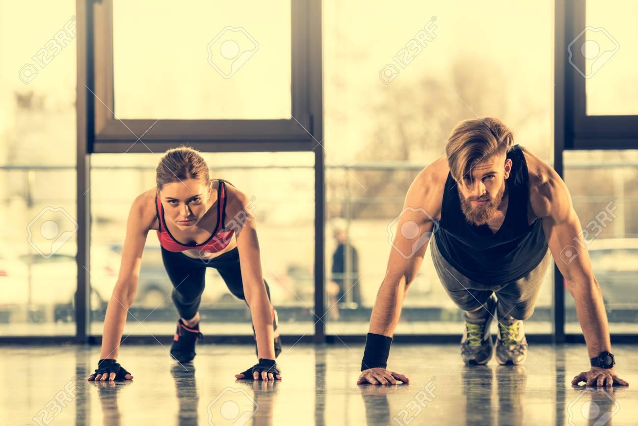 reputación primero gran descuento última selección Hombre atlético y mujer en ropa deportiva haciendo ejercicio tablón en el  gimnasio