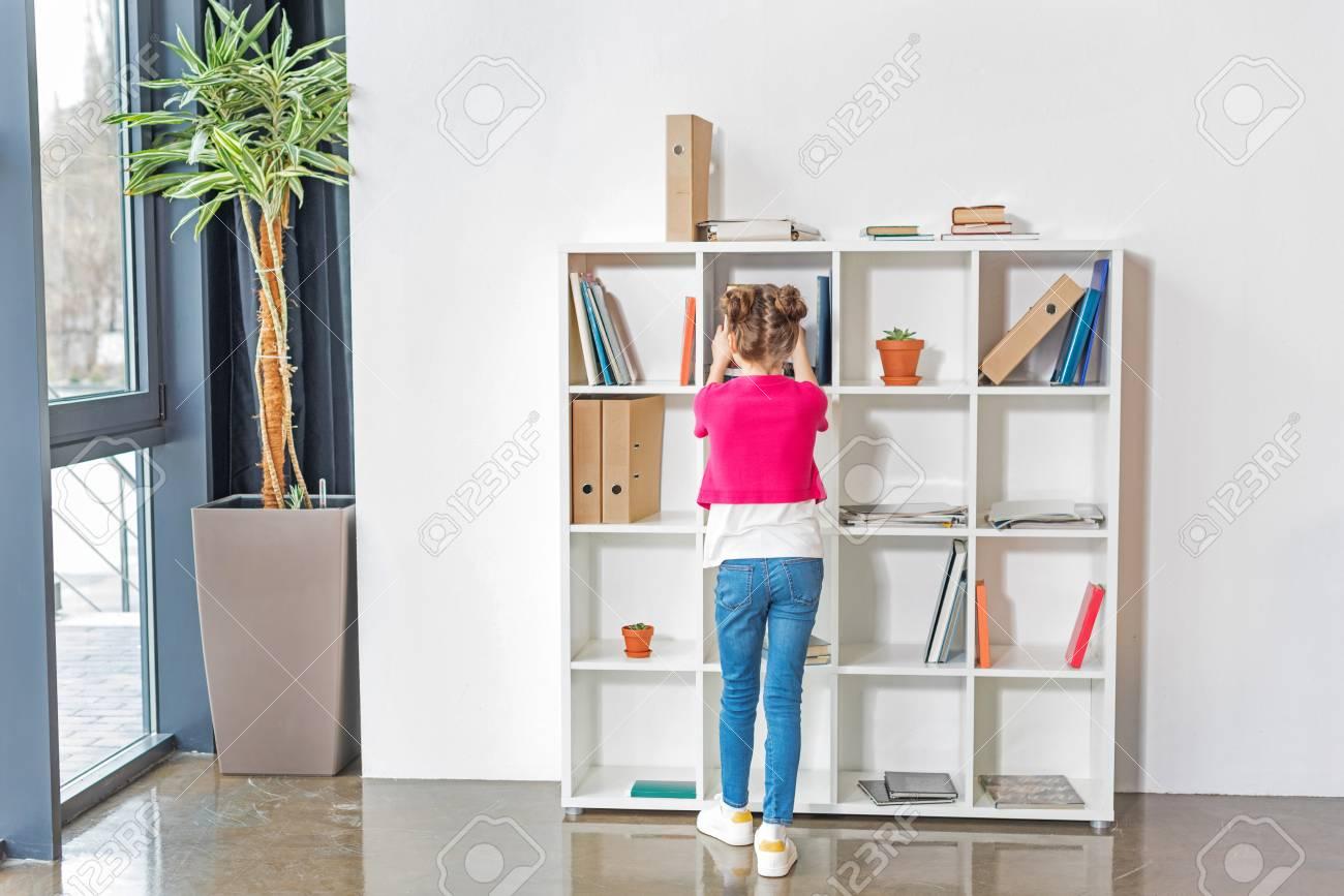 cute little girl choosing book on bookshelves stock photo 78106708 - Cute Bookshelves