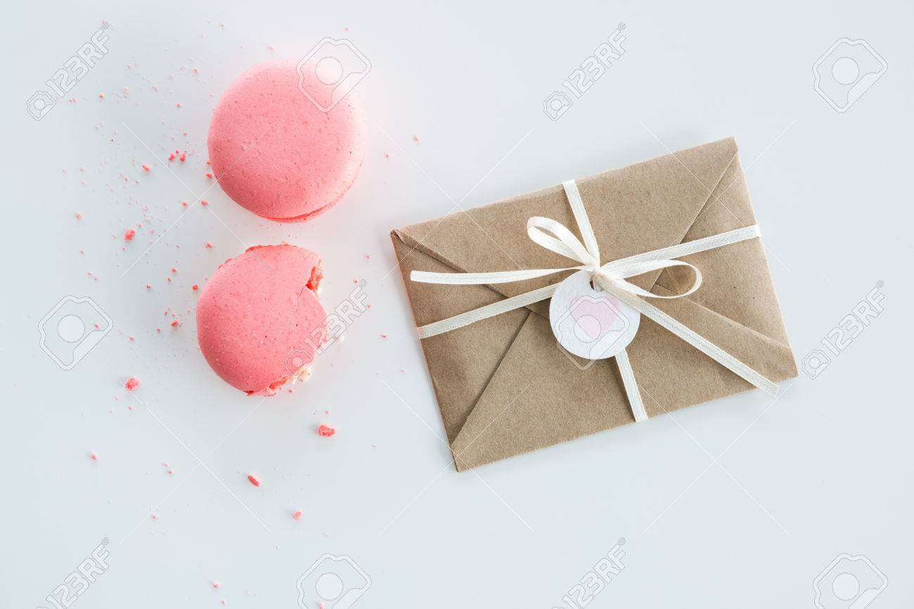 Top View Of Decorative Kraft Envelope With Bow And Pink Macarons ...